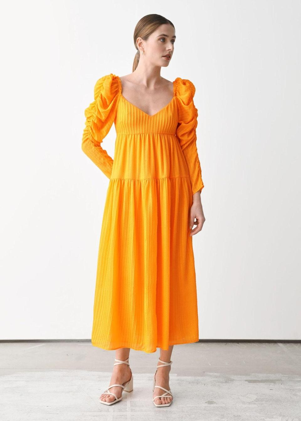 """Add some zest to the table in this puff-sleeve midi, which can work for an intimate brunch gathering or late lunch reception. Keep the vibes extra ~fresh~ with minimal accessories and an elegantly disheveled <a href=""""https://www.glamour.com/story/cord-knot-hairstyle?mbid=synd_yahoo_rss"""" rel=""""nofollow noopener"""" target=""""_blank"""" data-ylk=""""slk:cord knot bun"""" class=""""link rapid-noclick-resp"""">cord knot bun</a>. $249, & Other Stories. <a href=""""https://www.stories.com/en_usd/clothing/dresses/midi-dresses/product.mulberry-silk-puff-sleeve-midi-dress-yellow.0958620001.html"""" rel=""""nofollow noopener"""" target=""""_blank"""" data-ylk=""""slk:Get it now!"""" class=""""link rapid-noclick-resp"""">Get it now!</a>"""