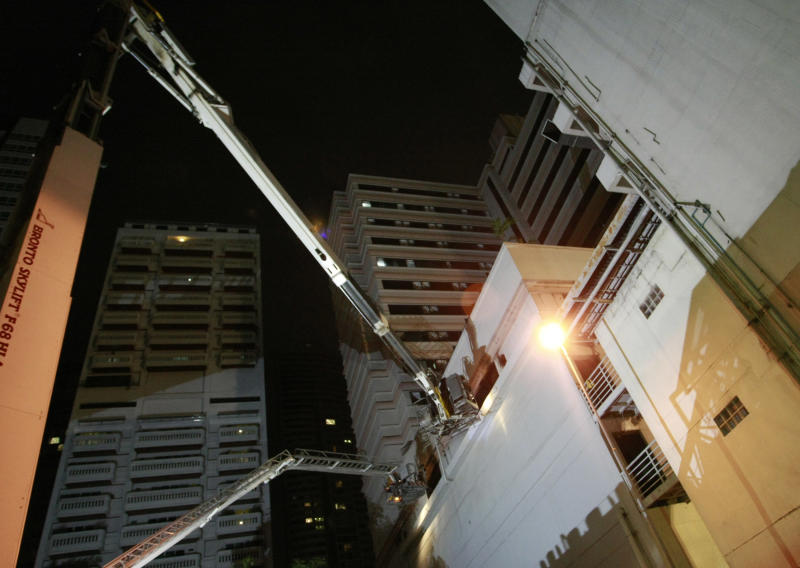 Firefighters in cranes search for people stranded on upper floors after a fire in a hotel Thursday March 8, 2012 in Bangkok, Thailand. A fire has burned part of a high-rise hotel in Bangkok's main tourist district. Firefighters rushed to the Grand Mercure Bangkok Park Avenue shortly before 10 p.m. Thursday and appeared to get the blaze under control. (AP Photo/Apichart Weerawong)