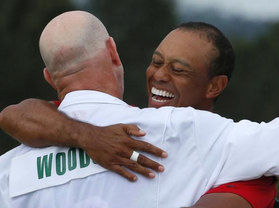 Tiger Woods celebrates winning the Masters with caddie Joe LaCava (Reuters)