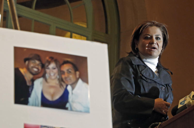 A picture of Arturo Rivera, right, with singer Jenni Rivera, center, and Jacobo Yabele, is displayed as Cynthia Rivera, Arturo's sister, far right, speaks at a news conference to announces a lawsuit on behalf of four associates of Mexican singer Jenni Rivera, who perished along with her in a plane crash in Mexico in December, Thursday, Jan. 10, 2013 in Los Angeles. Cynthia Rivera and Arturo Rivera are not related to Jenni Rivera. (AP Photo/Reed Saxon)