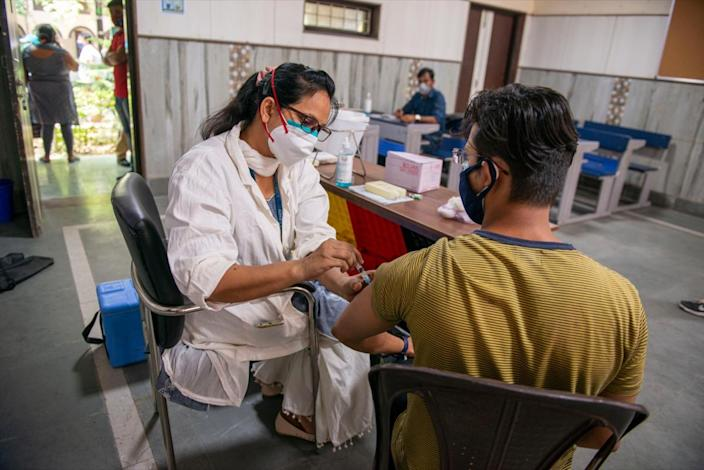 Man being vaccinated by a nurse in an Indian's mass vaccination site.