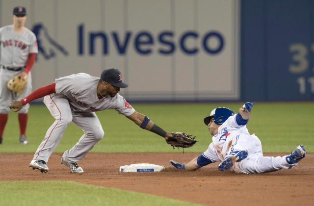 Toronto Blue Jays' Steve Pearce slides safely into second with a double as Boston Red Sox's Eduardo Nunez just misses with the tag during first inning baseball action in Toronto on Wednesday April 25, 2018. (Fred Thornhill/The Canadian Press via AP)
