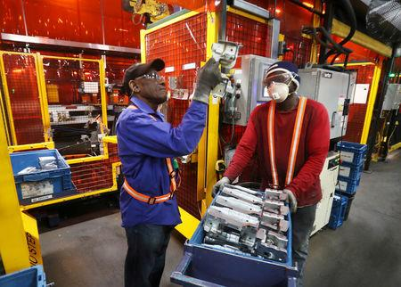 FILE PHOTO:    Workers examine parts for welding next to robot bay at Alfield Industries.