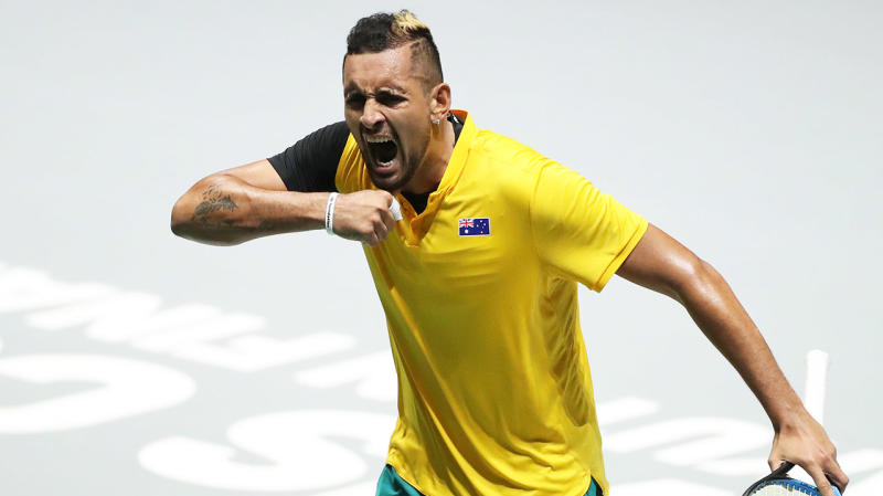 Nick Kyrgios pumps his chest as he celebrates after winning his tie against Belgium.