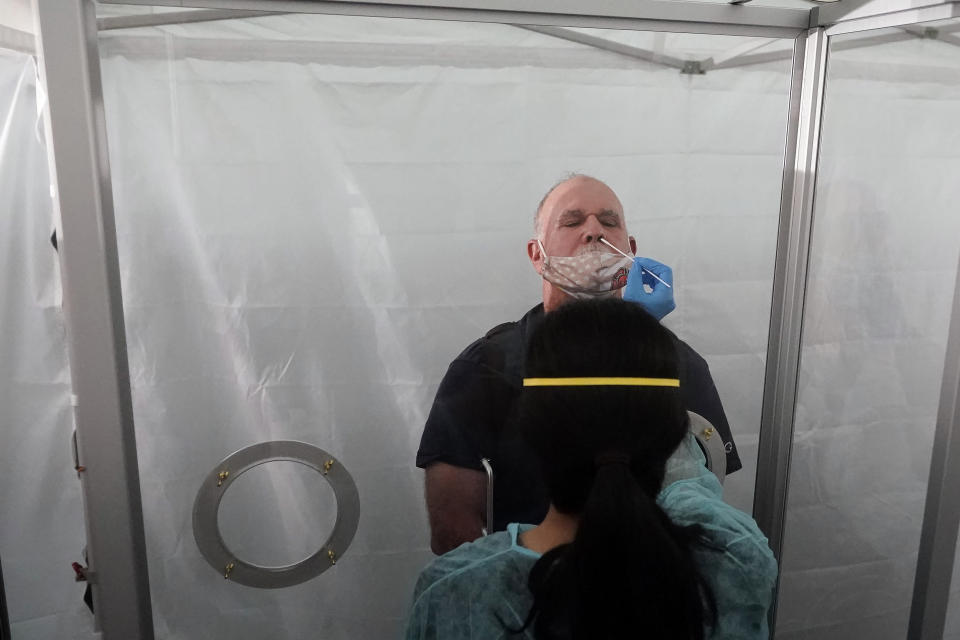 FILE - In this Oct. 15, 2020 file photo, Jim Zoller, top, gets a rapid COVID-19 test in San Francisco before a United Airlines flight from Hawaii on the first day of a Hawaii pre-travel testing program that allowed visitors to sidestep a quarantine rule with a negative COVID test. The small, tight-knit community of about 72,000 people on the island of Kauai in Hawaii spent the first seven months of the pandemic mostly COVID-free. Then in October, statewide travel restrictions eased and the island, which had only 61 known cases of coronavirus from March through September, went from zero cases to at least 84 new infections in just seven weeks. (AP Photo/Jeff Chiu, File)