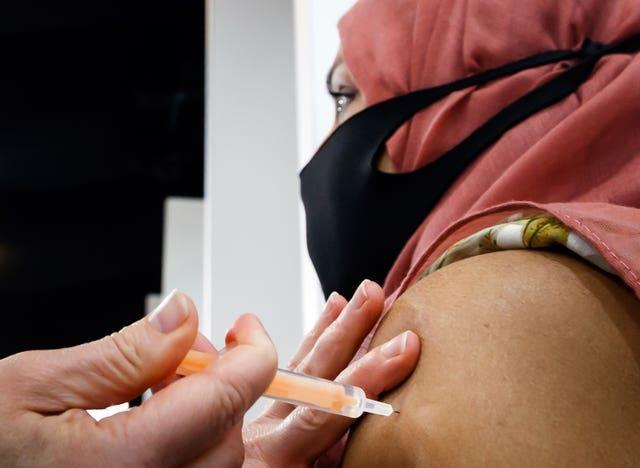 A woman receives an injection of the the Oxford/AstraZeneca coronavirus vaccine