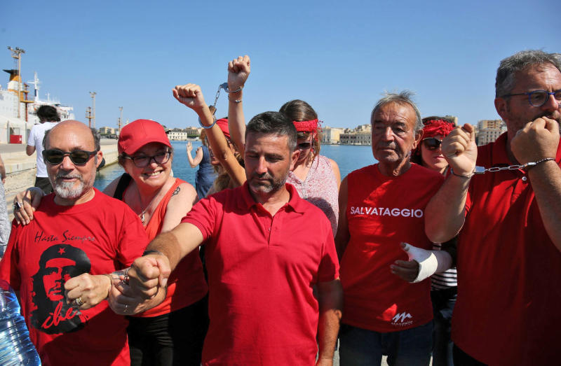 Activists wearing red T-sirts that symbolize a broader welcome to migrants, demonstrate by handcuffing their arms as they wait for the Italian Coast Guard ship Diciotti, with 67 migrants on board, to dock at the Sicilian port of Trapani, southern Italy, July 12, 2018. The ship is in the waters off Sicily awaiting permission to disembark its 67 migrants, some of whom are accused of threatening their rescuers if they were taken back to Libya. (Igor Petyx/ANSA via AP)