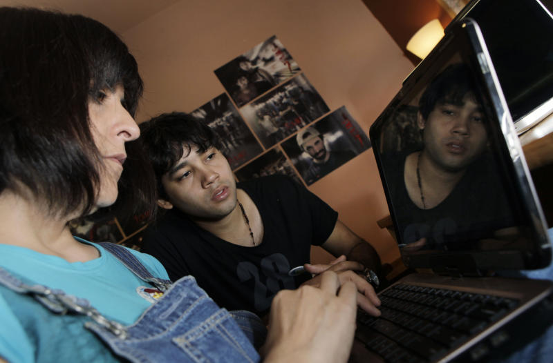 """In this Oct. 26, 2012 photo, Tana Schembori, from Paraguay, left, director of the Spanish language film """"7 Cajas"""", or """"7 Boxes,"""" works on the computer as actor Celso Franco looks on in Asuncion, Paraguay. The film is a new action movie featuring a poor delivery boy whose life depends on the mysterious cargo in his wheelbarrow has Paraguayans excited and proud to see their gritty reality on the big screen for the first time. (AP Photo/Jorge Saenz)"""