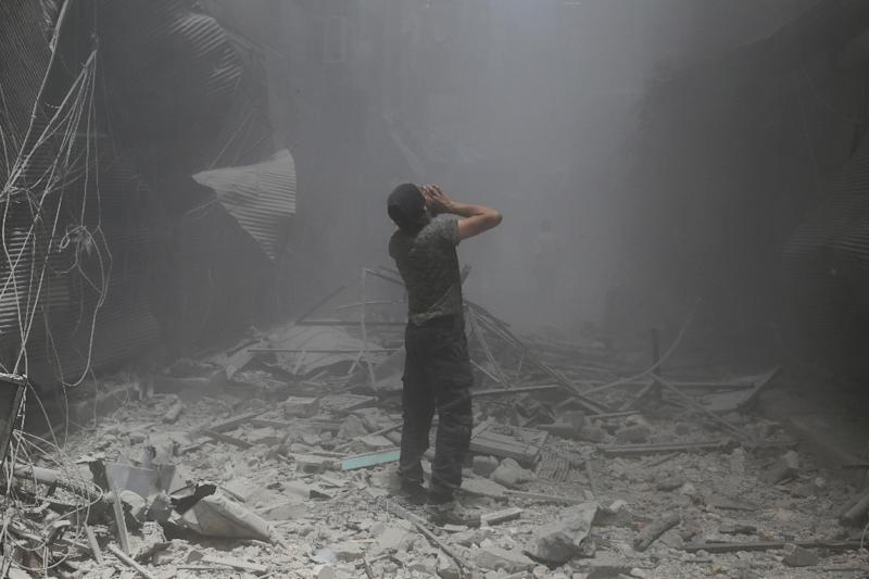 A Syrian man stands in rubble after a reported air strike by regime forces on the rebel-held neighbourhood of Bustan al-Qasr, on June 5, 2016