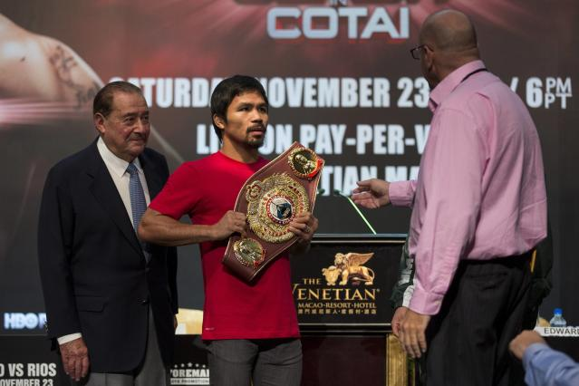 A staff member asks for the WBO International Welterweight Title belt back after Filipino boxer Manny Pacquiao (C) after a news conference at the Venetian Macao hotel in Macau November 20, 2013. Pacquiao will fight against American Brandon Rios in a 12-round welterweight clash on November 24. REUTERS/Tyrone Siu (CHINA - Tags: SPORT BOXING)