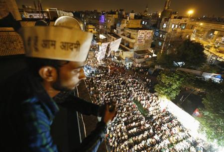 A supporter of the newly formed Aam Aadmi (Common Man) Party, stands on a residential building overlooking a public meeting being addressed by party leader Arvind Kejriwal, in New Delhi September 30, 2013. REUTERS/Mansi Thapliyal