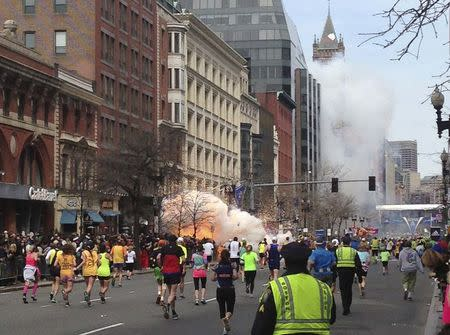 File photo of runners continueing to run towards the finish line as an explosion erupts at the finish line of the Boston Marathon