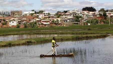 A man travels in a boat to fish in a pond in the outskirts of the capital Antananarivo
