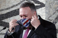 U.S. Secretary of State Mike Pompeo adjusts his face mask prior to a joint news conference with Italian Foreign Minister Luigi Di Maio in Rome, Wednesday, Sept. 30, 2020. Pompeo is in Italy as part of his six-day trip to Southern Europe. (Guglielmo Mangiapane/Pool Photo via AP)