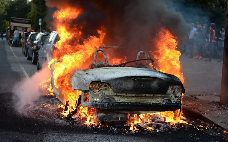 "A car is set alight during the ""Welcome to Hell"" rally against the G20 summit in Hamburg - Credit: AFP"