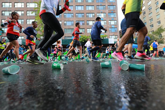 Runners pass discarded cups on First Avenue during the 2019 TCS New York City Marathon, Nov. 3, 2019 in New York City. (Photo: Gordon Donovan/Yahoo News)