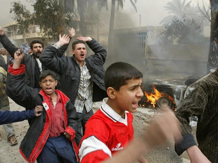 Iraqis in the street after an airstrike in Baghdad on 26 March 2003 (Goran Tomasevic/Reuters)