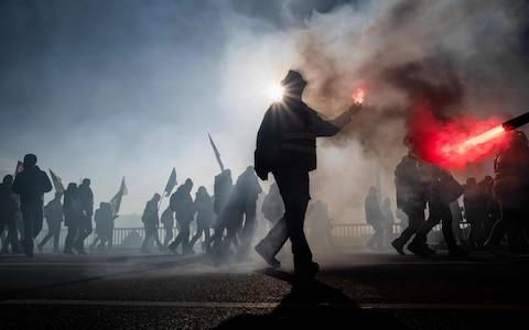 People light flares during a demonstration on December 10, 2019 in Lyon  - Credit:  JEFF PACHOUD/AFP