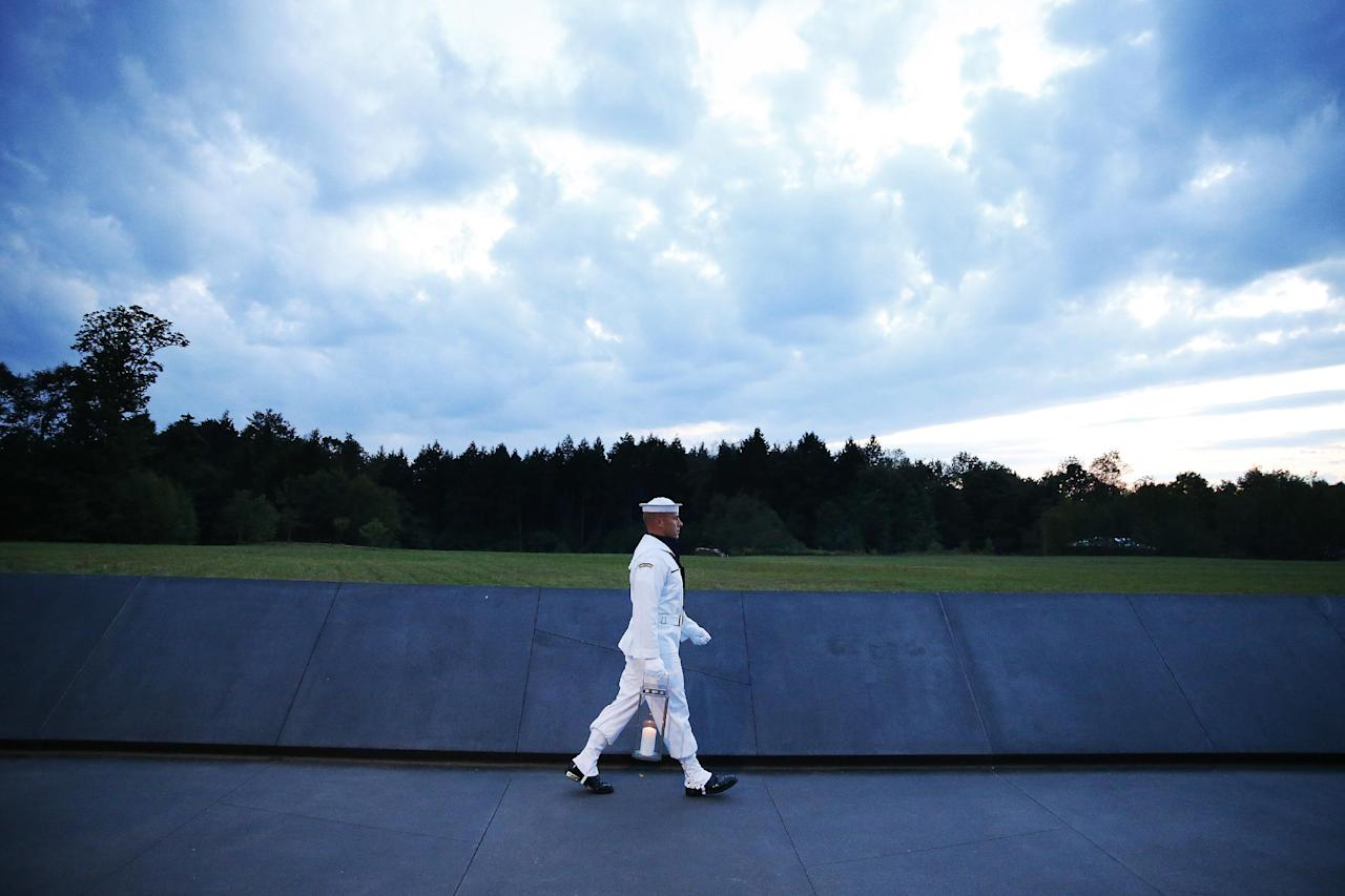 Candles in memory of the passengers and crew of Flight 93, are carried to the Wall of Names at the Flight 93 National Memorial in Shanksville, Pa, Saturday, Sept. 10, 2016, as the nation marks the 15th anniversary of the Sept. 11 attacks. (AP Photo/Jared Wickerham)