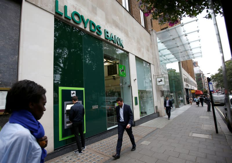 FILE PHOTO: People walk past a branch of Lloyds Bank at Berkeley Square in London
