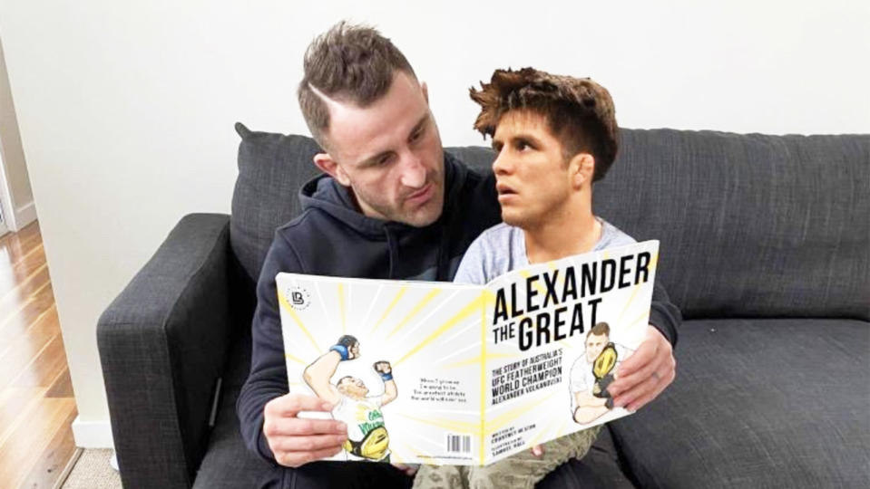 Alexander Volkanovski (pictured left) reading a book to a superimposed photo of rival Henry Cejudo (pictured right).