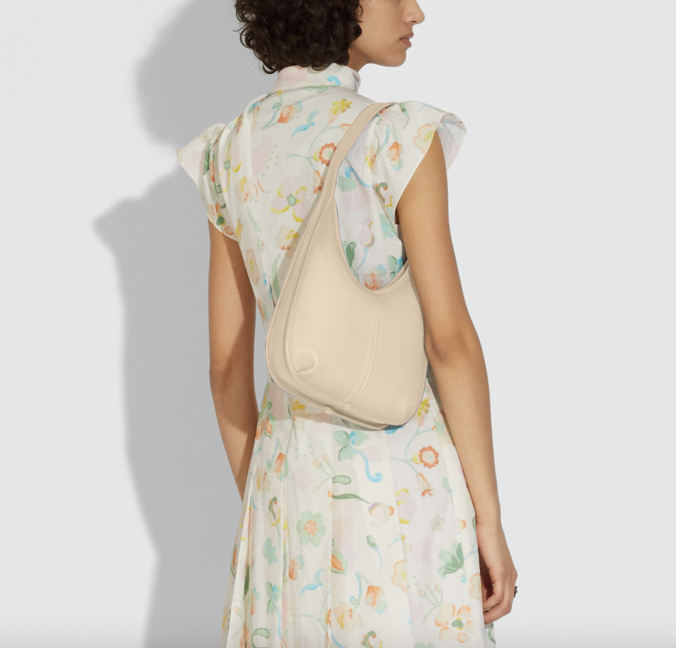 woman in white floral dress with coach Ergo Shoulder Bag in Ivory