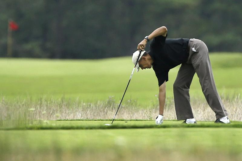 President Barack Obama places the ball before teeing off while golfing at Vineyard Golf Club in Edgartown, Mass., on the island of Martha's Vineyard Monday, Aug. 12, 2013. (AP Photo/Steven Senne)