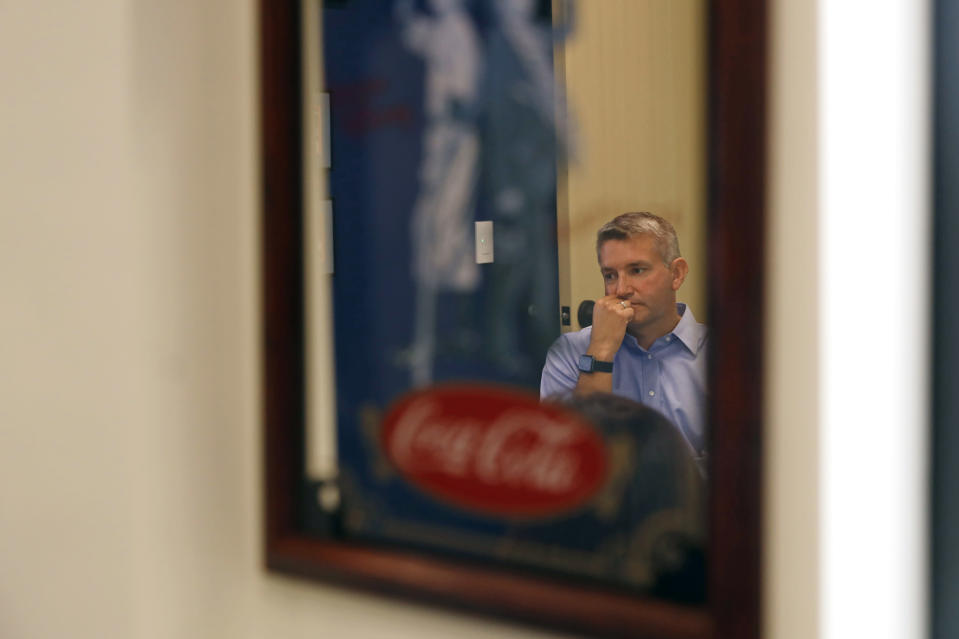 Ryan Smith, executive vice president of Ajinomoto Health and Nutrition North America, is reflected on a mirror as he listens during a company meeting at his office space in Itasca, Ill., Monday, June 7, 2021. Smith estimates 40% of the new headquarters design changed due to COVID. (AP Photo/Shafkat Anowar)