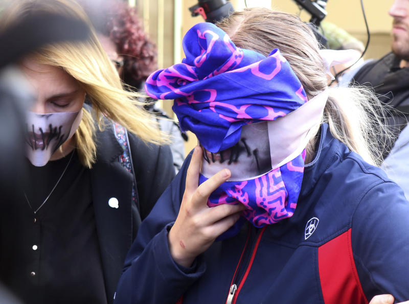 A 19-year old British woman, right, covers her face as she leaves from the Famagusta court after her trial, in Paralimni, Cyprus, Monday, Dec. 30, 2019. A Cyprus court on Monday found a 19 year-old British woman guilty of fabricating claims that she was gang raped by 12 Israeli men. (AP Photo/Philippos Christou)