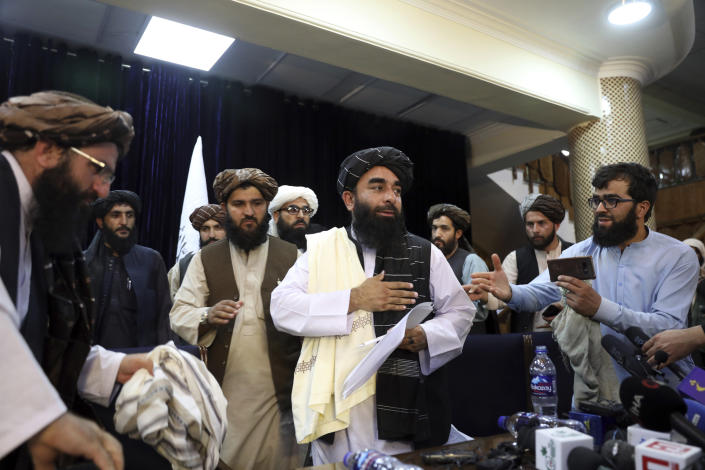Taliban spokesman Zabihullah Mujahid, center, leaves after his first press conference in Kabul, Afghanistan, on Tuesday, August 17, 2021. (Rahmat Gul / AP Photo)