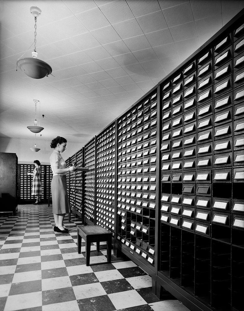 <p>Two young women are sorting computer punch cards in a room of filling cabinets. Long before files were digitized and available on the cloud, documents had to be carefully sorted and organized in a physical location. Workers need to stay on top of where everything is kept in order to maintain smooth operations at the office. </p>