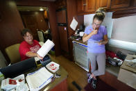 Angela Collins, of Pleasantville, Iowa, right, fills out an information sheet for a COVID-19 vaccination shot for her son Jesse James, Monday, Aug. 16, 2021, in Des Moines, Iowa. At the Iowa State Fair in Des Moines, where a million people are expected for the 11-day event, public health officials hope a vaccination station set up by pharmacists working for the Hy Vee food store chain will entice some of the vaccine-hesitant to get their shots. Visitors are packing in to state fairs in multiple Midwest states as COVID activity is increasing, raising concerns about the potential for rapidly accelerating spread of the delta variant of the COVID-19 virus. (AP Photo/Charlie Neibergall)
