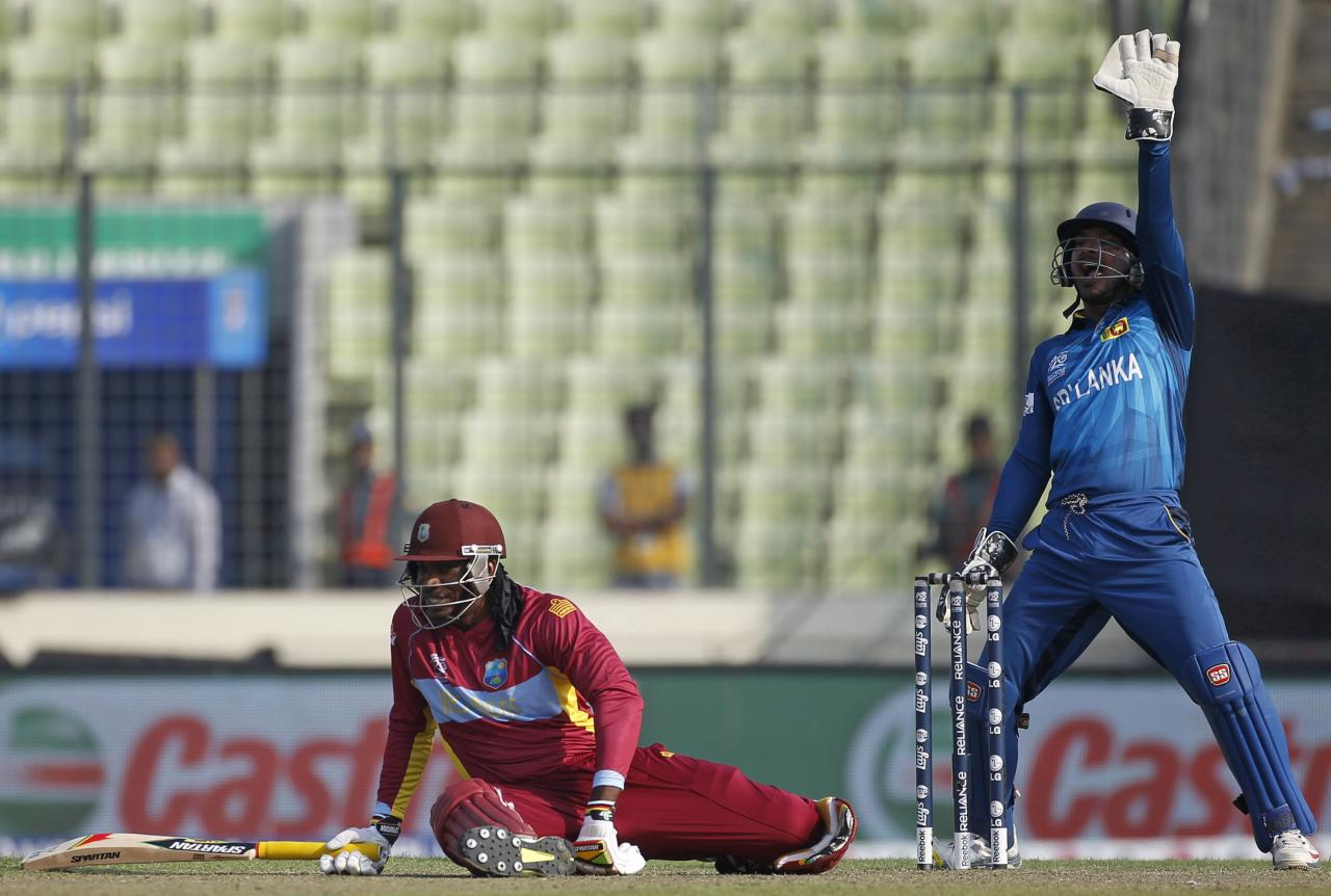 West Indies Chris Gayle (L) falls on ground as Sri Lanka's wicketkeeper Kumar Sangakkara appeals for his dismissal unsuccessfully during their warm-up match of ICC Twenty20 World Cup at the Sher-E-Bangla National Cricket Stadium in Dhaka March 19, 2014. REUTERS/Andrew Biraj (BANGLADESH - Tags: SPORT CRICKET)