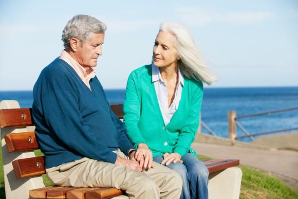 Senior couple sitting on a bench near the water