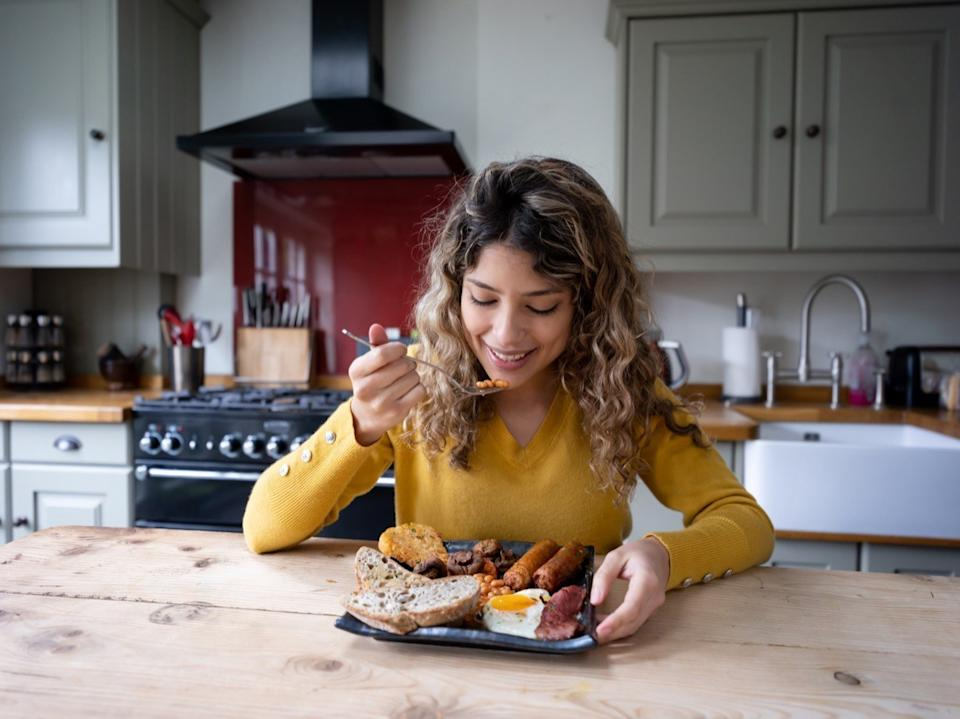Beautiful young woman at home enjoying a delicious english breakfast