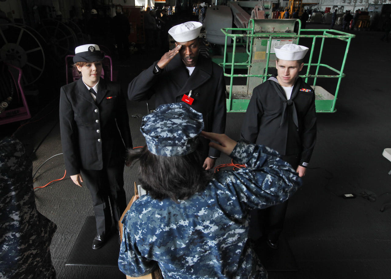 In this March 8, 2012 photo, identification checkers, Kelley Bright, left, Ikecchukw Okpara, center, and Colten Brown, right, salute a sailor as she arrives aboard the nuclear powered aircraft carrier USS Enterprise at the Norfolk Naval Station in Norfolk, Va. The ship will begin it's final deployment this Sunday, March 11. The ship's storied 50-year history includes action in several wars, a prominent role in the Cuban missile crisis and serving as a spotter ship for John Glenn's orbit of the Earth. (AP Photo/Steve Helber)