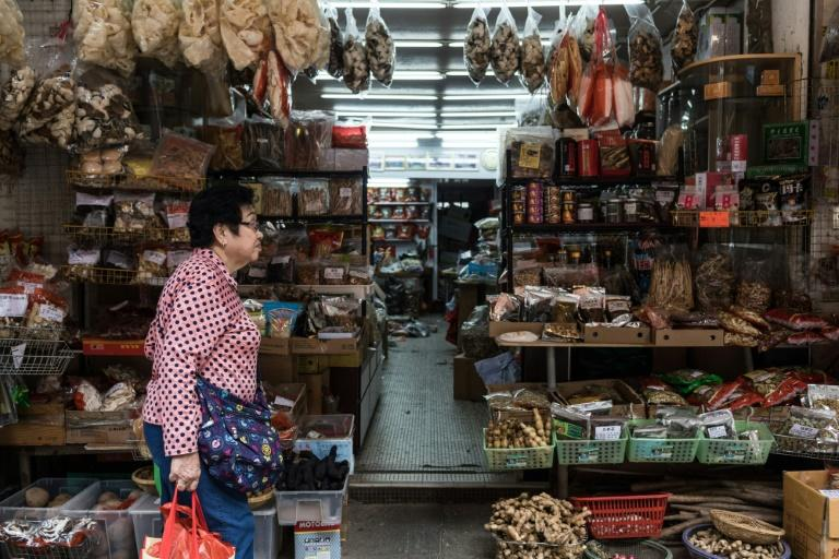 A woman walks past a shop on a street popular for dried foods used in traditional Chinese medicine and dishes in Hong Kong
