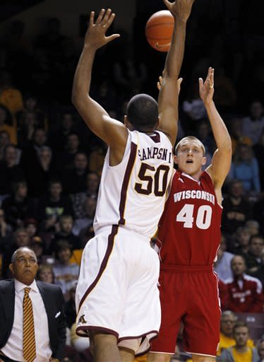 Wisconsin's Jared Berggren (40) hits a 3-point shot against Minnesota's Ralph Sampson III (50) during the first half of an NCAA college basketball game Thursday, Feb. 9, 2012, in Minneapolis. At rear is Minnesota coach Tubby Smith. (AP Photo/Genevieve Ross)