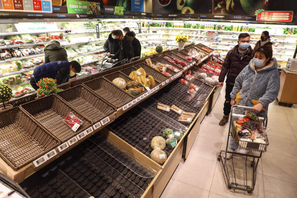 FILE - In this Jan. 25, 2020, file photo, shoppers wearing face masks look for groceries with many empty shelves at a supermarket in Wuhan in central China's Hubei province. The Chinese city of Wuhan is looking back on a year since it was placed under a 76-day lockdown beginning Jan. 23, 2020. (Chinatopix via AP, File)