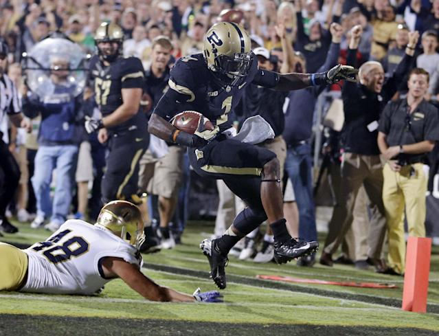 Purdue running back Akeem Hunt, right, goes over Notre Dame linebacker Dan Fox on his way to a touchdown during the first half of an NCAA college football game in West Lafayette, Ind., Saturday, Sept. 14, 2013. (AP Photo/Michael Conroy)