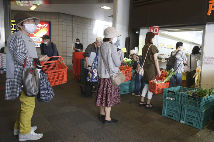 People wearing face masks to protect against the spread of the new coronavirus keep social distancing as they wait to enter a fruit and vegetable shop in Yokohama, near Tokyo, Tuesday May 12, 2020. (AP Photo/Koji Sasahara)