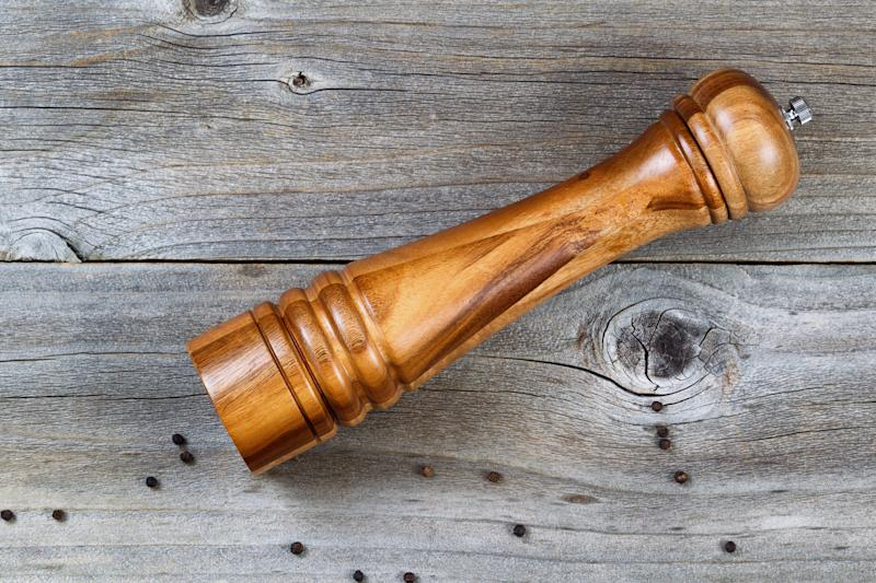 Top view shot of Wooden Pepper Mill with whole black pepper spilled on Rustic Wood