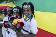 Children hold flowers to greet the arrival of Ethiopia's Prime Minister Abiy Ahmed, ahead of a final campaign rally, in the town of Jimma in the southwestern Oromia Region of Ethiopia Wednesday, June 16, 2021. The country is due to vote in a general election on Monday, June, 21, 2021. (AP Photo/Mulugeta Ayene)