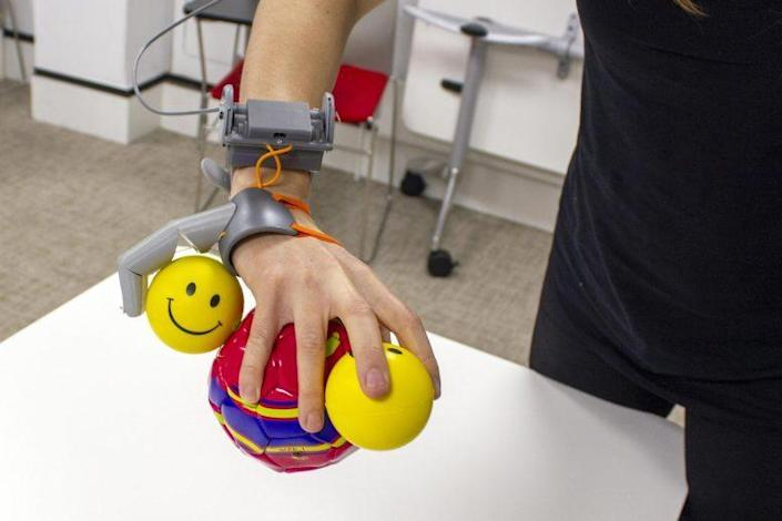 Third Thumb works in tandem with the real hand to hold several toy balls at once.
