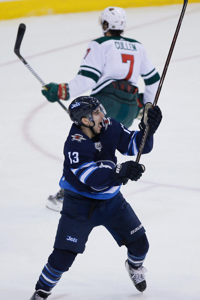 Winnipeg Jets' Brandon Tanev (13) celebrates his goal, as Minnesota Wild's Matt Cullen (7) skates away during the first period in Game 5 of an NHL hockey first-round playoff series in Winnipeg, Manitoba, Friday, April 20, 2018. (John Woods/The Canadian Press via AP)
