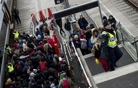 Police organize the line of refugees at on the stairway leading up from the trains arriving from Denmark at the Hyllie train station outside Malmo