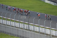 Athletes compete during the men's cycling road race at the 2020 Summer Olympics, Saturday, July 24, 2021, in Oyama, Japan. (AP Photo/Christophe Ena)