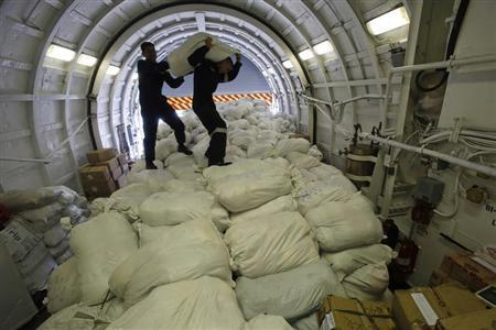 Members of the Philippine Navy carry a sack containing relief goods before transporting them to the battered town of Tacloban city, inside the latest warship BRP Ramon Alcaraz docked in Manila