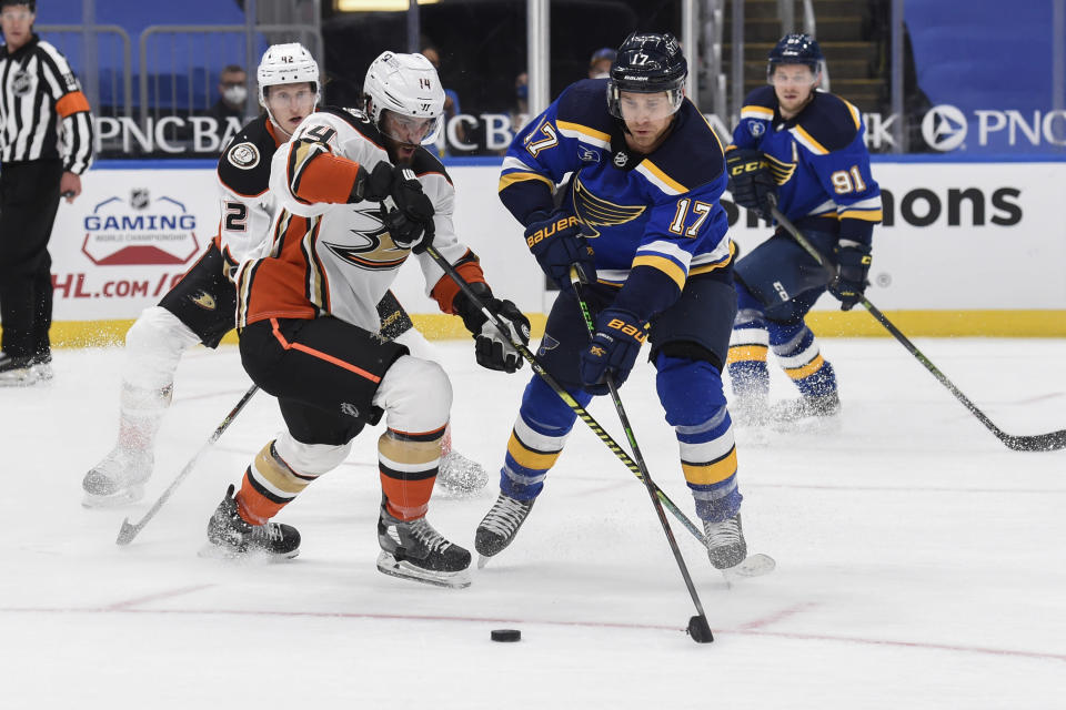 Anaheim Ducks' Adam Henrique (14) and St. Louis Blues' Jaden Schwartz (17) compete for the puck during the second period of an NHL hockey game Friday, March 26, 2021, in St. Louis. (AP Photo/Joe Puetz)