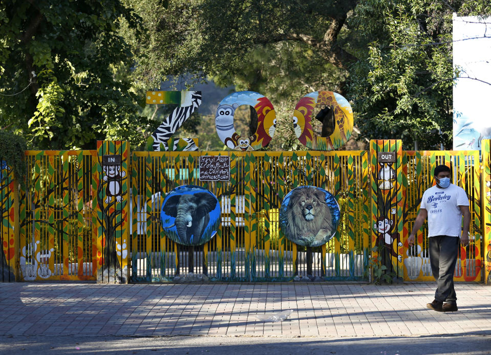 A Pakistani walks past the main gate of the Marghazar Zoo which is officially closed to the public, in Islamabad, Pakistan, Wednesday, Dec. 16, 2020. A pair of sick and neglected dancing Himalayan brown bears will leave Islamabad's notorious zoo Wednesday for a sanctuary in Jordan, closing down a zoo that once housed 960 animals. The Marghazar Zoo's horrific conditions gained international notoriety when Kaavan, dubbed the world's loneliest elephant, grabbed headlines and the attention of iconic American entertainer Cher. (AP Photo/Anjum Naveed)